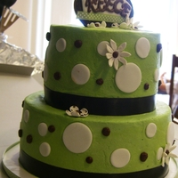 Polka Dots And Flowers  Buttercream cake with fondant and gumpaste decorations and some buttercream polka dots. Gumpaste/fabric ribbon topper. Satin ribbon borders...