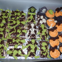 Halloween Treats Brownies with candy skeleton (idea from Wilton) and cupcakes with candy skulls and picks. My first time playing with candy melts, it was...