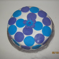 Blue And Purple Pound cake with buttercream icing and blue and purple fondant circles, and a blue and purple fondant flower in the middle