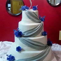 Royal Blue And Silver Four tier wedding cake (5,8,11 & 14). The largest I have made so far. BC finish with royal blue gumpaste roses and silver fondant...