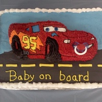 Cars Baby Shower Cake 12x18 cake with Wilton Lightening Mc Queen cake on top. Car is star tipped with a pacifier in his mouth. Cars cake and bottom cake are iced...