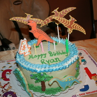 Dinosaur Cake Chocolate chip cake filled with cookie dough and Bettercream. Covered with vanilla frosting and sugar cookies with royal icing details.