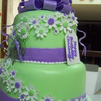 Purple And Green Birthday Cake Chocolate cake covered with fondant. Fondant daisies and gelatin butterfly. Thanks for looking.