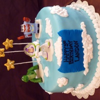 Buzz Lightyear / Toy Story  Toy Story Buzz themed cake covered in MMF with royal icing clouds. Stars are made of modeling chocolate with pixie dust glitter. Banner is...