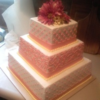 Watermelon Colored Wedding Cake Buttercream with fondant ribbons and silk flowers