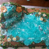 "Luau  Made for a baby showe. 2 11x15 cakes and a 10"" square carved for the waterfall. Buttercream with fondant flowers and piping gel to..."