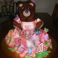 Taehas 1St Birthday Cake 3D Bear on a picnic blanket, surrounded by butterflies and bugs. Nappy made out of fondant