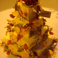 Fall Wedding Cake. Hand made leaves.. I made around 300 of them.. A big chrysanthemum on the top.. The colors matched the leaves that were on the brides...