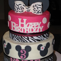 Minnie Mouse & Zebra Stripes Minnie mouse cake , zebra ribbon around each tier . Bow is fondant with zebra stripes . Minnie were cut out using cricut cake .