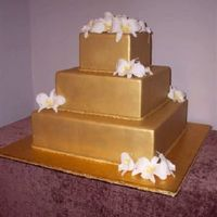 Gold With Orchids Fondant sprayed with gold and white gumpaste orchids with canary throats.