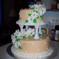 Wilton Course 3 Final Cake This is a tiered cake made with lots of large and small lillies and leaves.