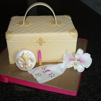 Luggage Bag Cake With Accessories Cake is covered in fondant and all accent pieces (handkerchief, mirror compact and lipstick) are made out of 50/50. Orchid is made out of...
