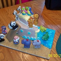 Noah's Ark Covered with fondant. The animals are the Fisher Price toys. The board was done with graham cracker and piping gel. Thanks for looking