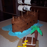 Pirate Ship Cake  Cake was chocolate with chocolate butter cream frosting, covered in white MMF then wood planks were stuck onto the white for the wood ship...