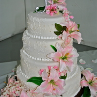Cascading Lillies This is an 8 inch, 10 inch, 12 inch, 14 inch round tiered cake covered in Michelle Foster's Fondant. The leaf pattern was drawn by...
