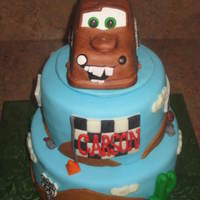 Mater Desert Cake MMF covered cake... RKT Mater covered in MMF and gumpaste decorations. Gumpaste for the road signs and I hand-painted them with food...