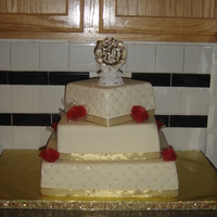 50Th Wedding Anniversary covered in white chocolate mmf, edible gold pearls and hand made chocolate clay roses. Top and bottom tier is white cake with chuncky...