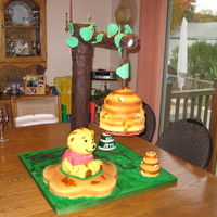 Beehive/winnie The Pooh Cake  I made this cake for my cousin's 1st birthday. The beehive, winnie and honeycomb are all made out of cake covered in fondant. The tree...