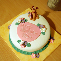 Birthday Cake With A Dog Chocolate cake, covered with fondant. Puppy and flowers are made from gumpaste.