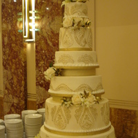 Art Deco Ivory And Gold Wedding Six tier ivory buttercream 24KT gold designs. Fresh flowers.