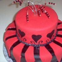 Black & Red Birthday Two Tiered, black and red chocolate cake. Covered with fondant, iced with buttercream. Beaded Wire cake topper. Hand painted accents on 2nd...