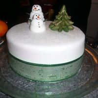 "Snowman Cake  8"" Madeira Sponge cake, iced with buttercream, filled with custard, and covered with fondant. Hand sculpted fondant Trees and Snowmen..."