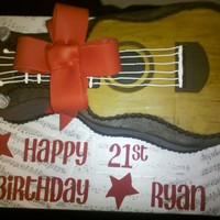 Guitar Cake   Chocolate cake, chocolate icing, fondant guitar and bow. Used 2 layers of the Wilton's guitar pan.