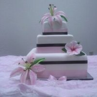 Hibiscus And Lily Wedding Cake 16, 12, and 8 inch squares covered in MMF, satin ribbon, gumpaste star gazer lily and hibiscus.