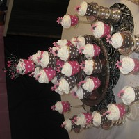 029_1254794574.jpg Cupcake sculpture I made for ladies tea....Chocolate cupcakes vanilla Buttercream with pink and black gumpaste daisies!