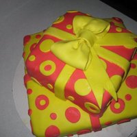 Yellow And Red Presents A half yellow half chocolate cake with buttercream and covered with MMF I made for a friend's birthday.