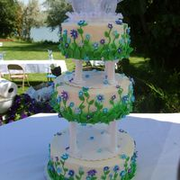 Gavin Cake This cake was covered in buttercream and had blue and puple fondant flowers of different size in the cake with green leaves at the bottom...