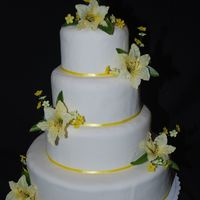 Spring Wedding This is a fondant covered cake with yellow lilies and misc flowers.