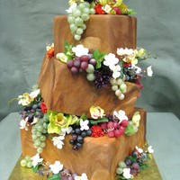Grape Vine Cake this is a topsy turvy cake with marbleized fondant to give it a wood look. In between each layers there are grapes and orchids and a...