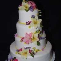 Easter Wedding This a fondant covered cake with yellow and pink lilies and misc colored flowers cascading down the cake.