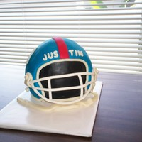 Ny Giants Football Helmet Chocolate cake, torted with buttercream, coated with ganache and then covered with fondant. My first time making a helmet cake.