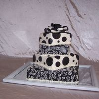 Black And White Wedding Cake   This is a 4 tier wedding cake, 12,9,7, and 5 inches. It was for a small wedding so it's not huge but it fit the occasion.