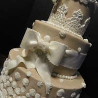 Vintage Buttercream with fondant bow and vintage buttons and lace appliques.Gumpaste flowers for topper