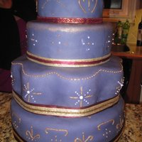 Purple And Gold Celebration fondant covered cake, with gold and purple piping (the purple looks white because ofthe flash). ribbon details, and a gold carnation as a...