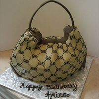 Gucci Purse Cake This cake is covered in buttercream. All the G's are hand-pipped and the purse hardware is made of fondant :)