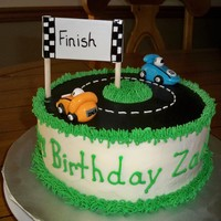 Race Care Cake   8 inch round buttercream. Road made of fondant. Cars fondant and gumpaste