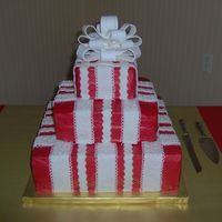 Present Wedding Cake This was my second wedding cake I've done. It is iced in red buttercream with white fondant ribbons to resemble a present. It was very...
