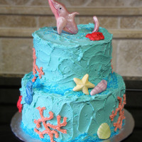 Sea Themed Cake This sea themed cake has a pink dolphin jumping out of the top, crabs, seahorses, shells and coral.