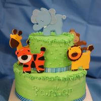 Baby Shower- Animal A 2-tier Jungle theme baby shower cake. BC icing, ribbon around the bottom of the tiers & wooden cutouts of animals that I found. I...