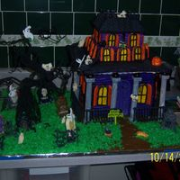 Haunted House Scary, spooky haunted house made of gingerbread walls and roof, candy graveyard figurines, and buttercream icing
