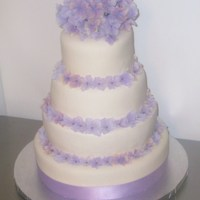 Lilac Flower Wedding Cake This is a 4-tier fondant cake adorned with lilac color flowers.