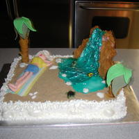 A Day At The Beach Pink Champagne cake with Champagne butter cream icing. Sun bather is 50/50 fondant and gum paste. Palm Trees are pretzels w/ 50/50 fondant...