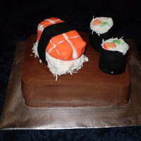 Sushi Cake Cake covered with buttercream icing and sushi rolls made with fondant. TFL!
