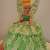 Tinkerbell Birthday Cake This cake was made with a barbie type cake pan and covered in fondant leaves with the Tinkerbell barbie doll inserted in the middle.