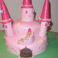 "Pink Castle Cake 10"" round cake covered in pink fondant icing. second tier 6"" round cake. pillars made out of swiss roll covered in icing. spires..."