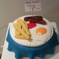 "Egg And Chips Cake 8"" round sponge cake covered in fondant icing, table cloth made from blue fondant icing. chips and sausages made from marzipan egg and..."